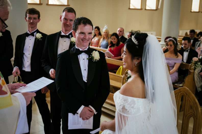 groom smiling at bride at alter