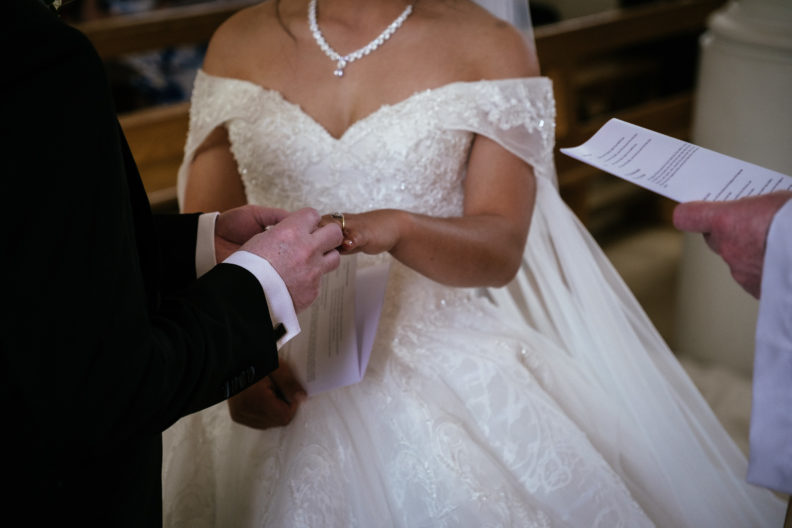 groom placing wedding ring on bride
