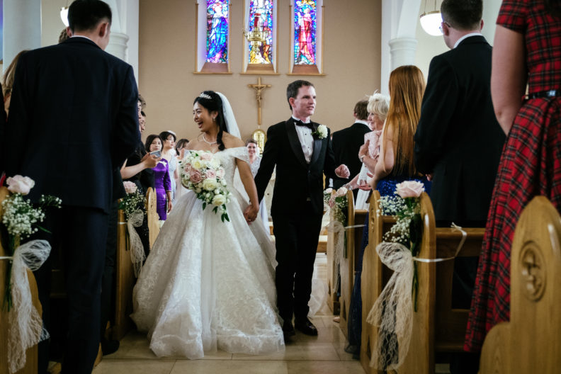 bride and groom walking down aisle of church