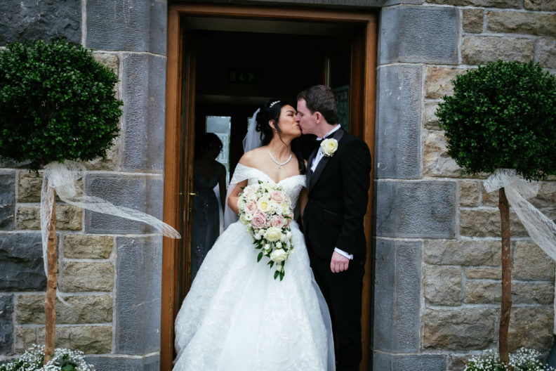 bride and groom kissing at door of church after getting married