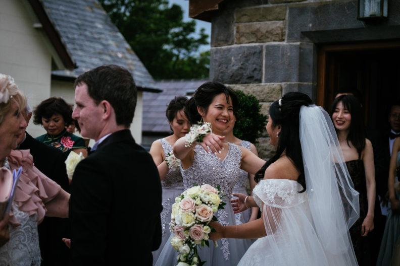 wedding guest hugging bride in churchyard