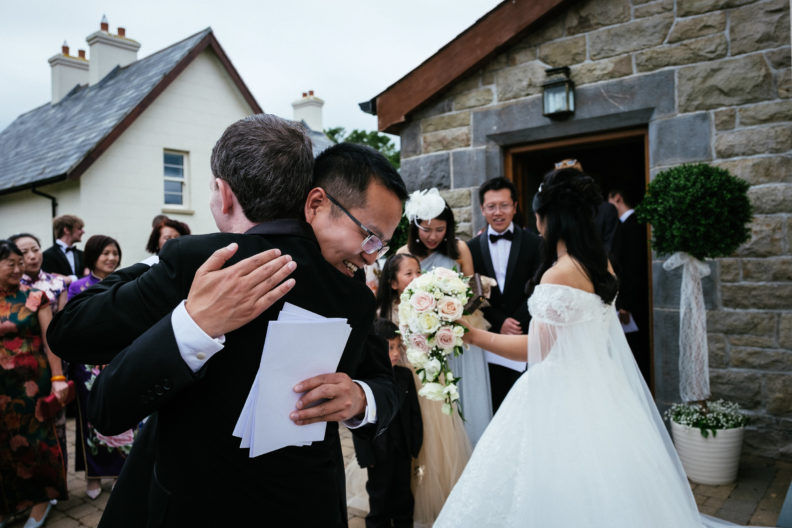 wedding guests hugging groom