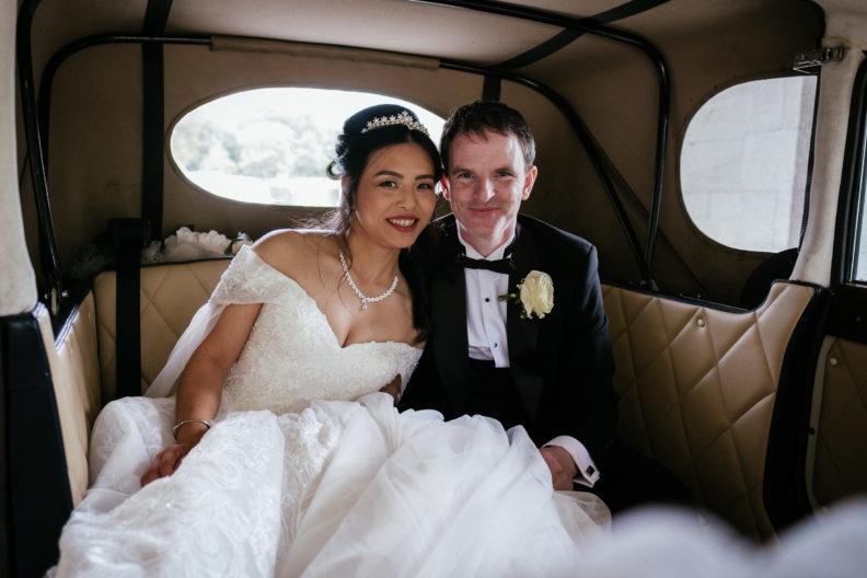 bride and groom min back of vintage wedding car