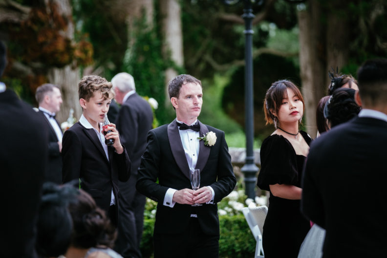 groom standing with wedding guests