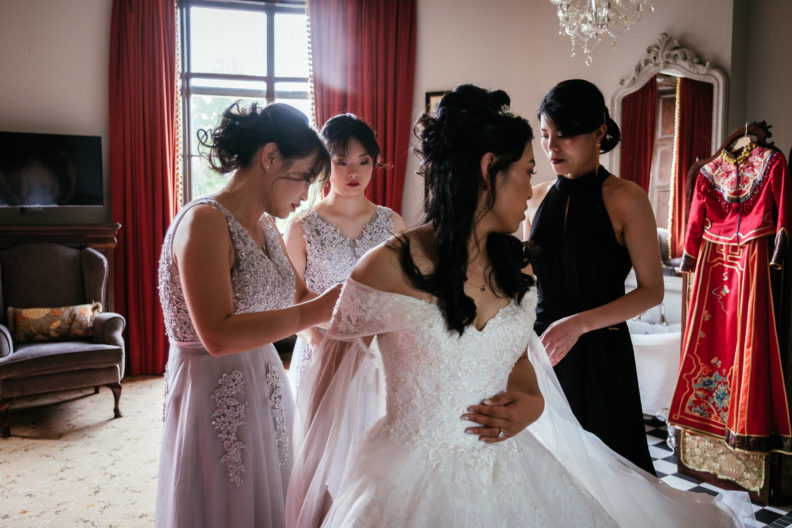 bride being fitted into her dress