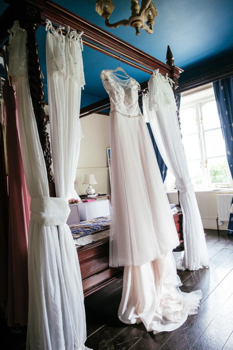 brides dress hanging at end of bed