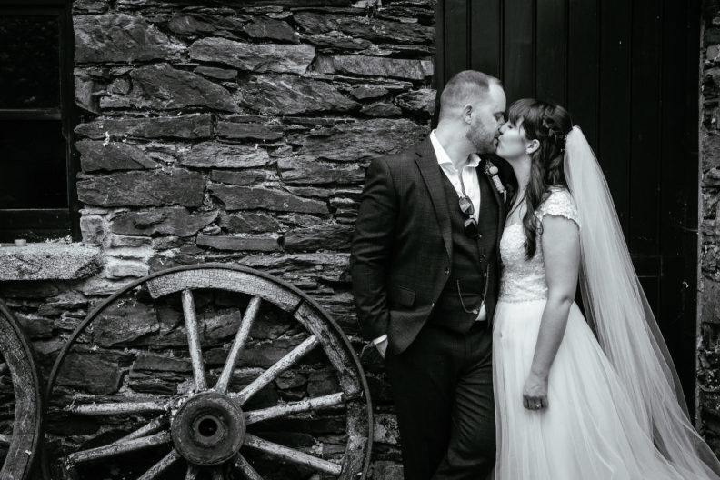 bride and groom standing kissing by a wall in ballybeg house