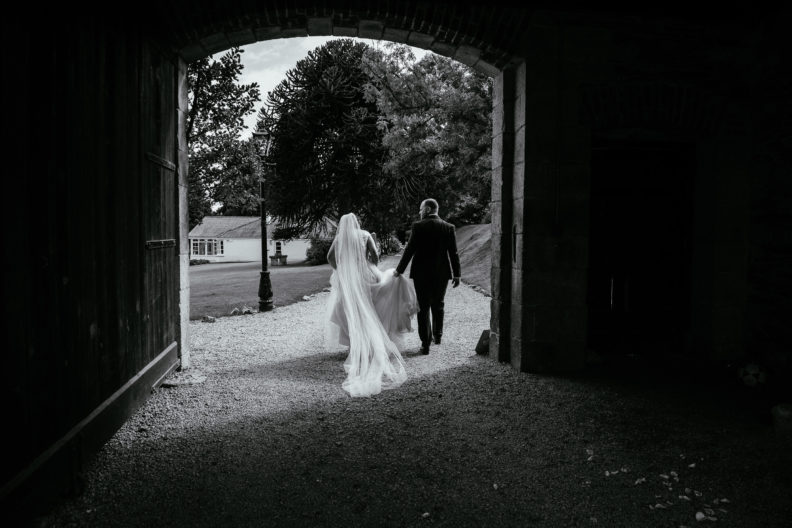 bride and groom walking down avenue bride and groom sitting and standing in bar of ballybeg house