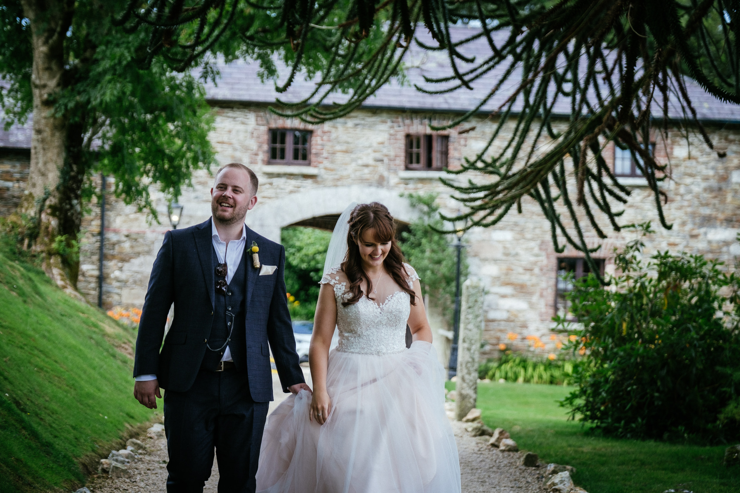 bride and groom walking under trees at ballybeg house