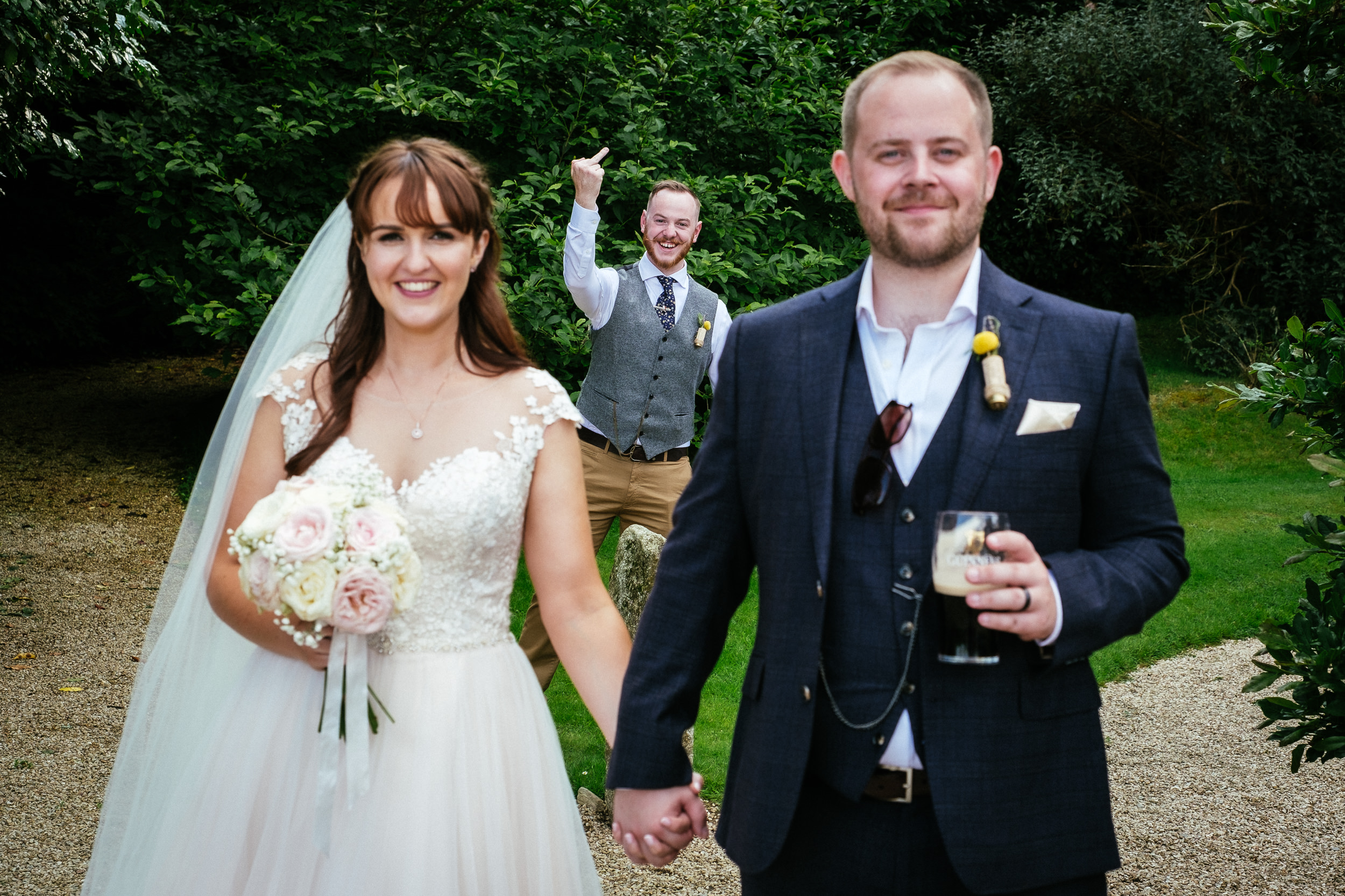 bride and groom posing with guest gesticulating behind them