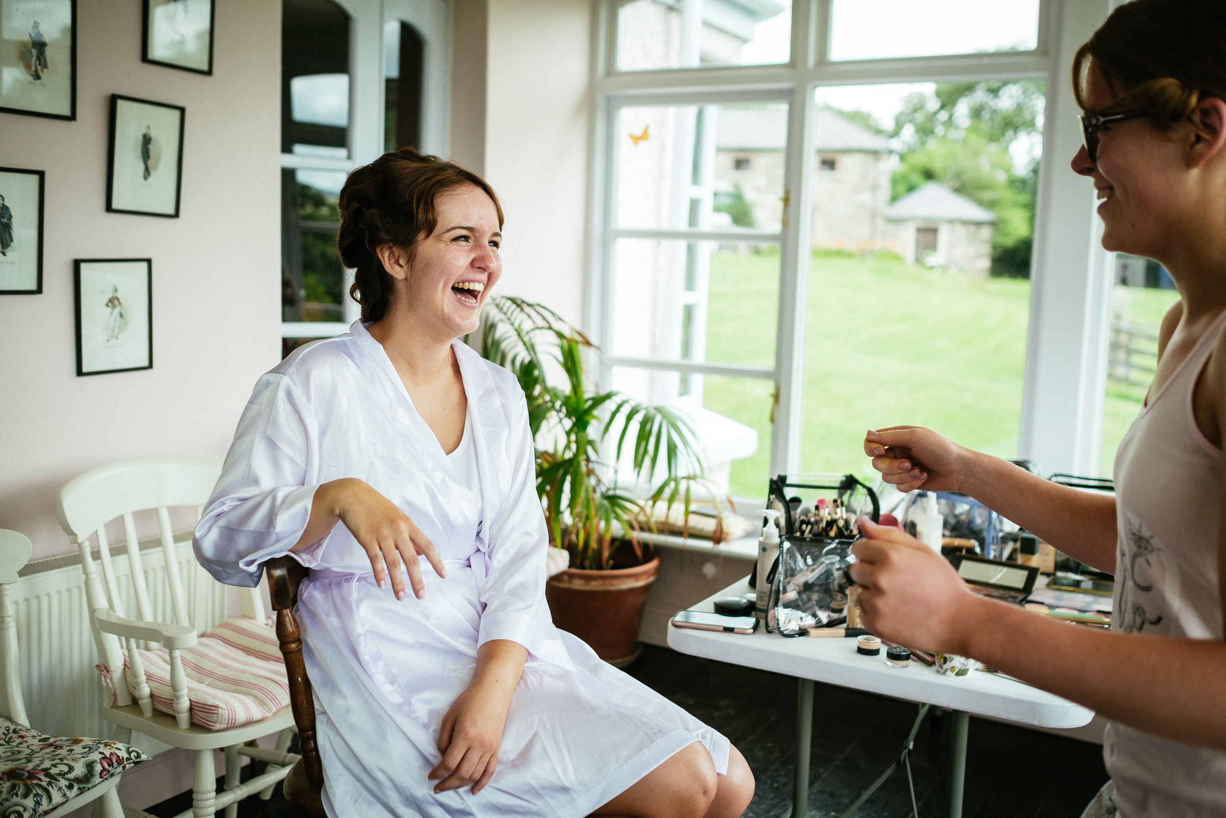 bride sitting in makeup chair laughing