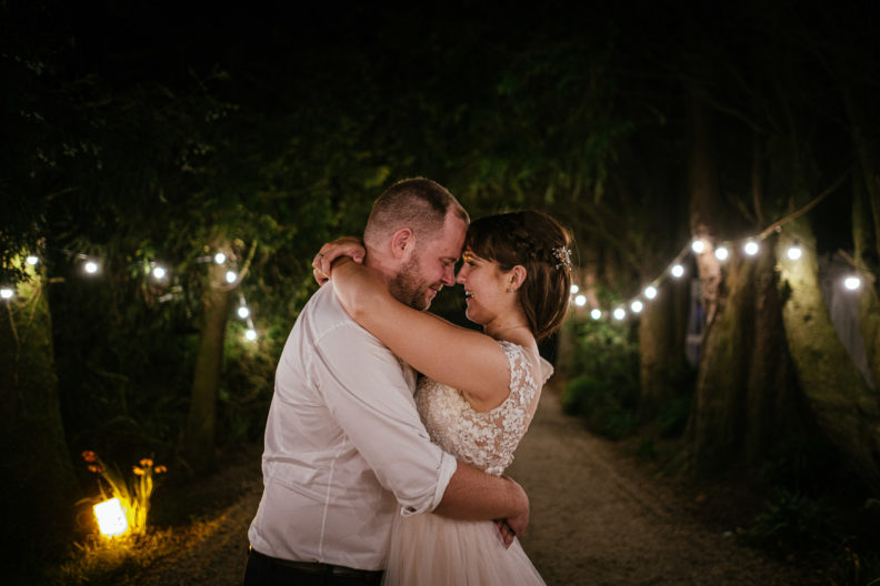 bride and groom embracing under lightbulbs at ballybeg house wicklow