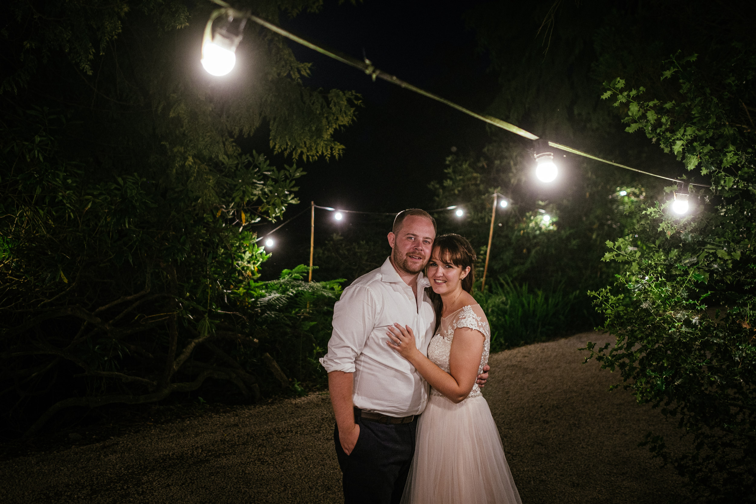 bride and groom embracing under lightbulbs and smiling at camera at ballybeg house wicklow