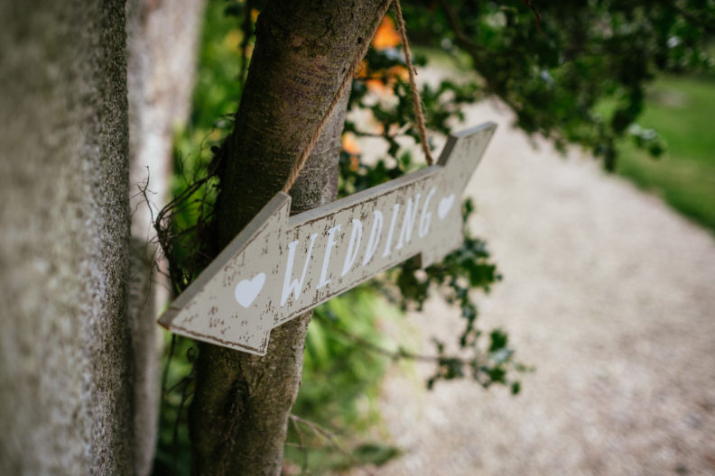 wooden arrow pointing to direction of civil wedding ceremony