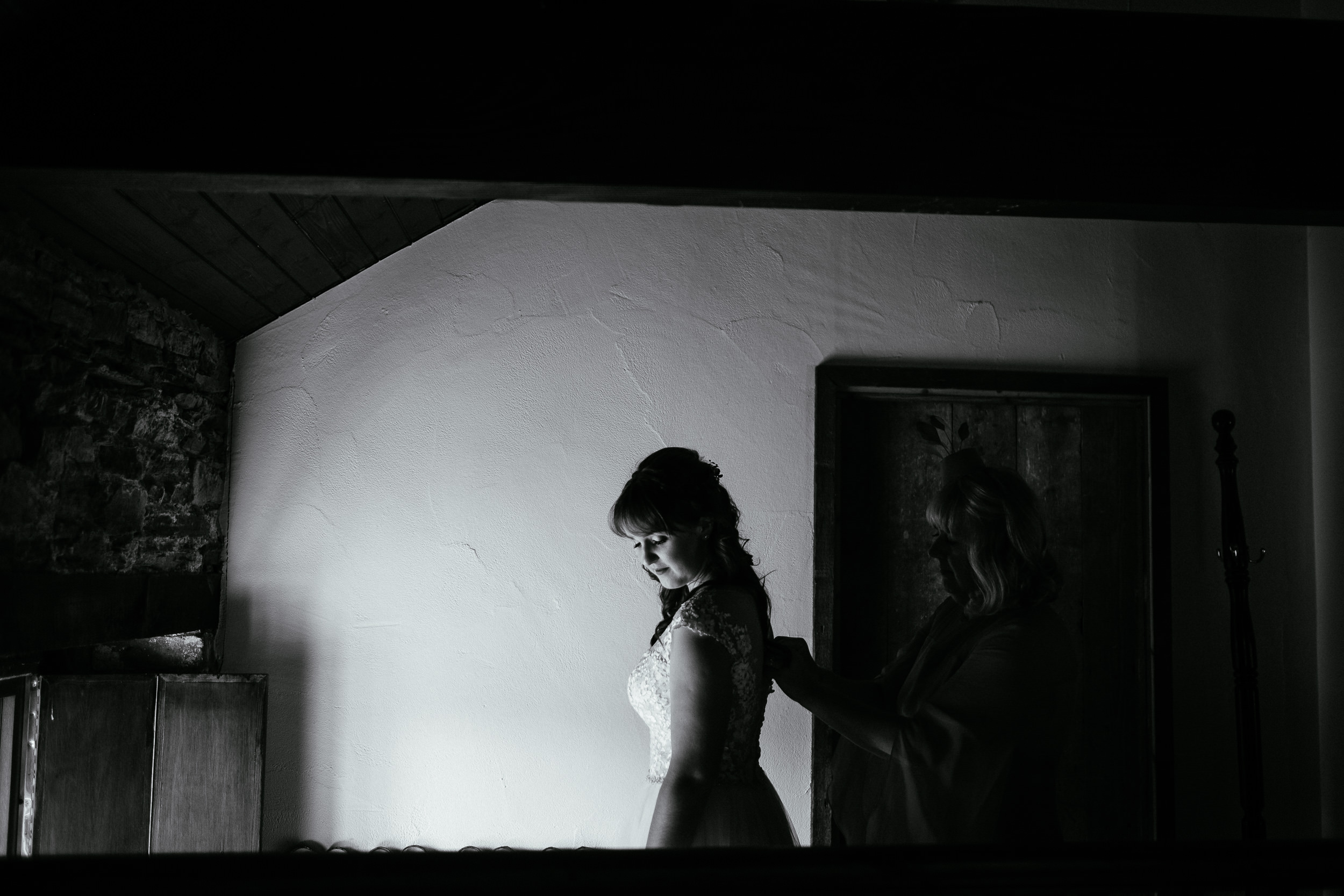 bride being buttoned into her dress by her mother