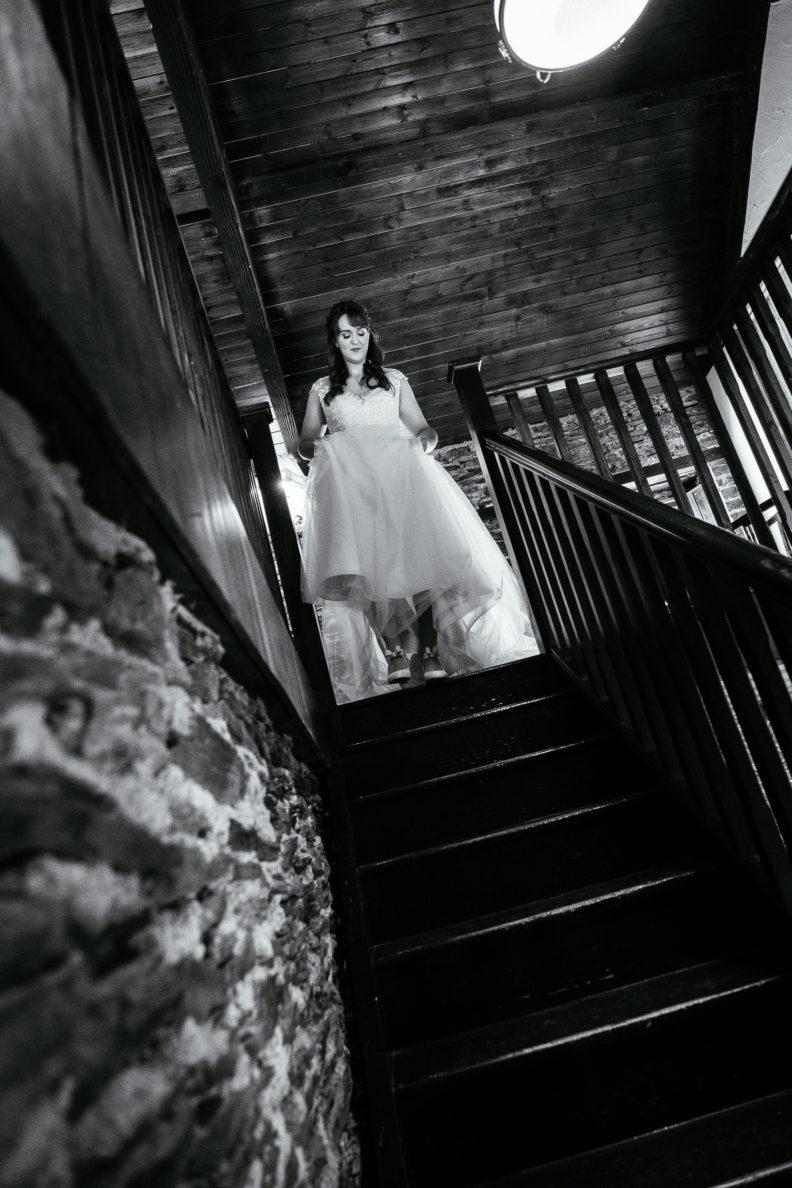 bride walking down stairs holding her dress