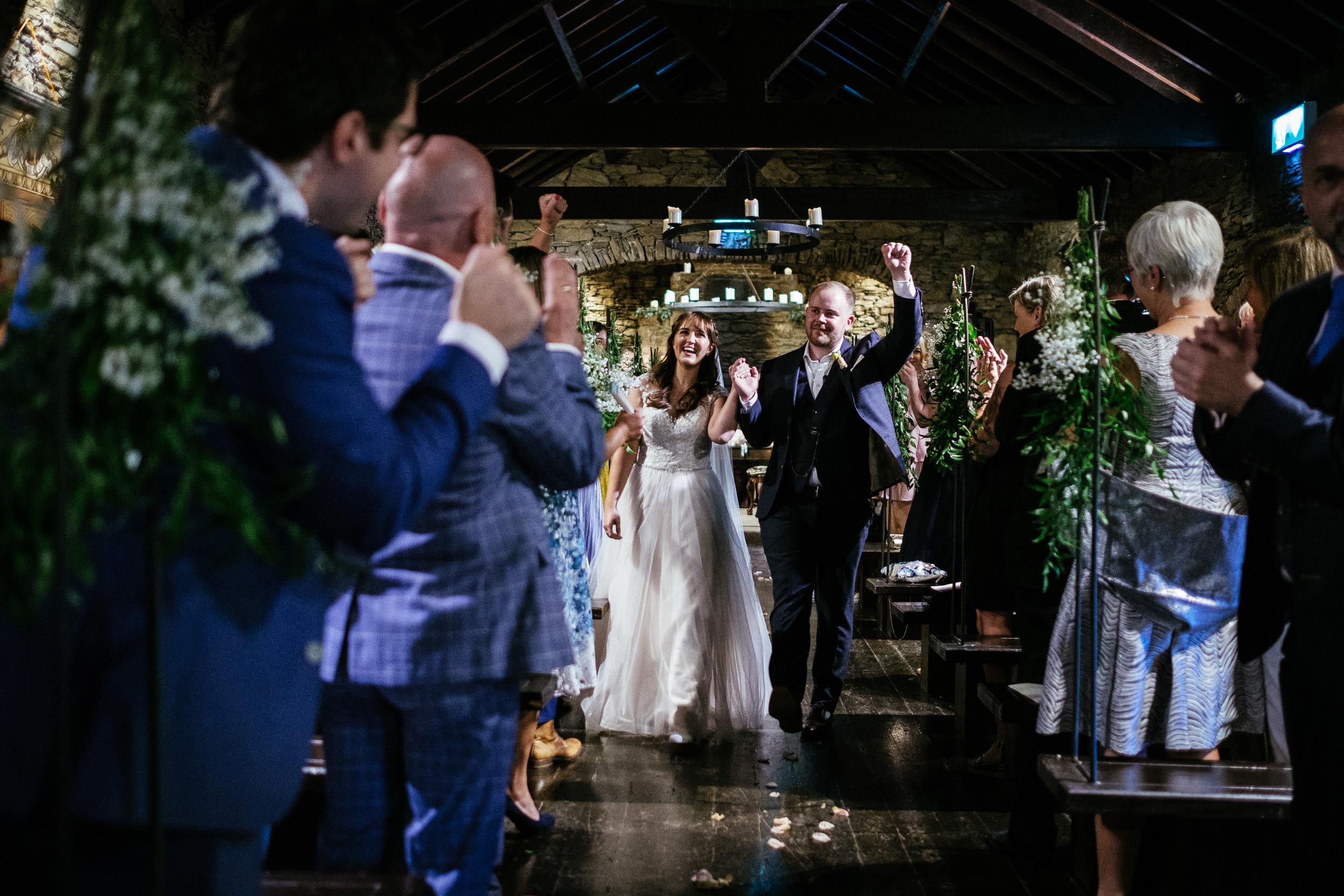 bride and groom walking down aisle in barn at ballybeg house