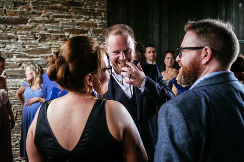 groom laughing with wedding guests