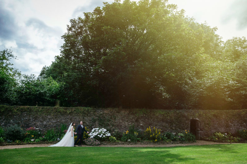 bride and groom walking in garden of ballybeg house with sunflare