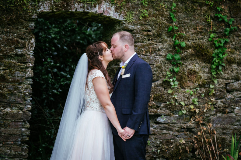 bride and groom kissing in garden of ballybeg house