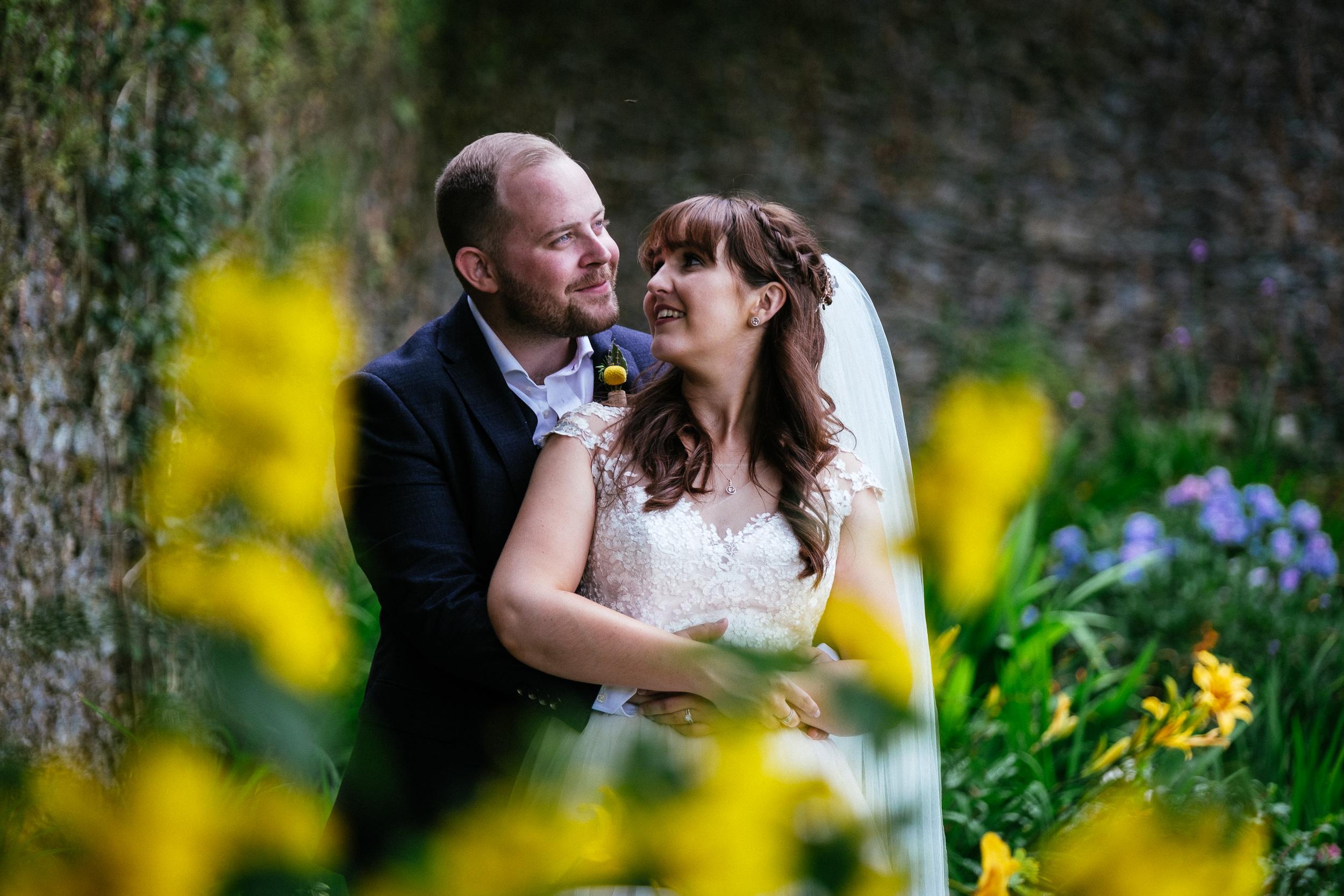 bride and groom embracing in garden of ballybeg house