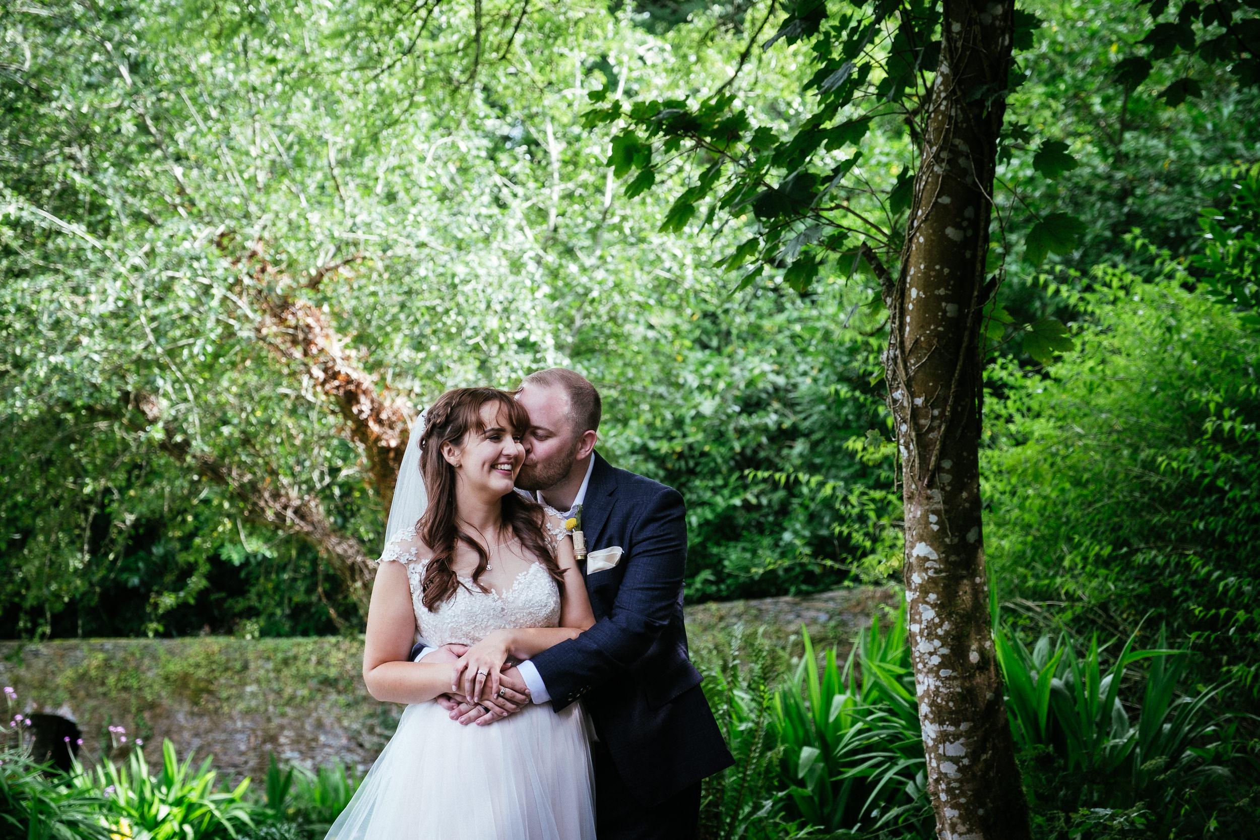 bride and groom hugging in garden of ballybeg house