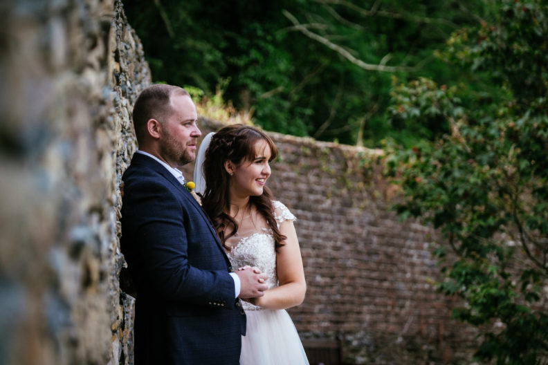 bride and groom standing by a wall in ballybeg house