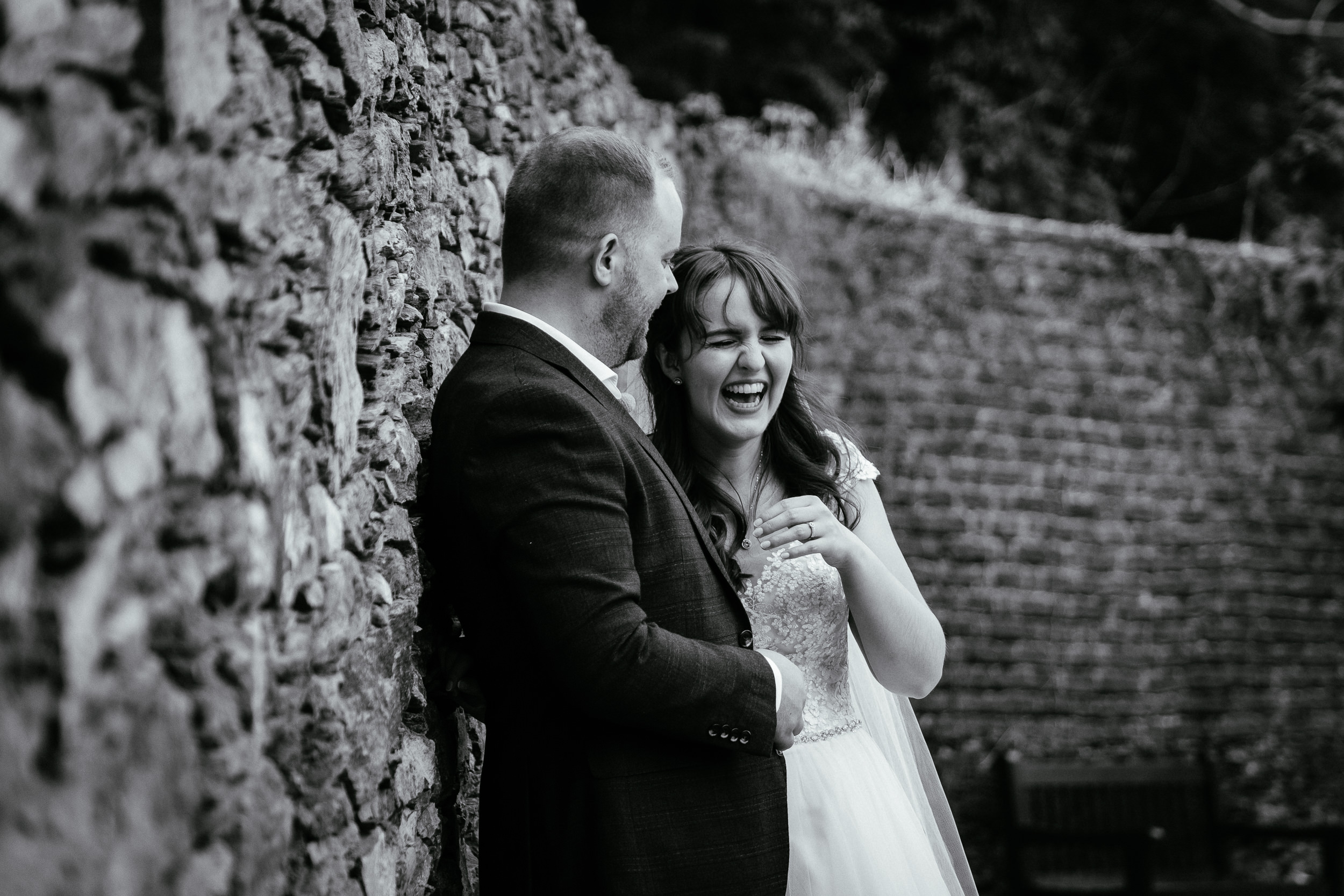 bride and groom laughing by a wall in ballybeg house