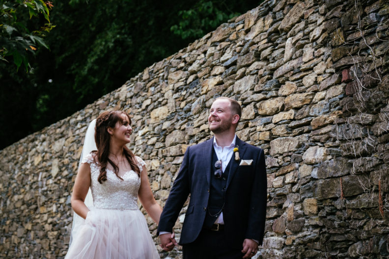 bride and groom strolling by a wall in ballybeg house