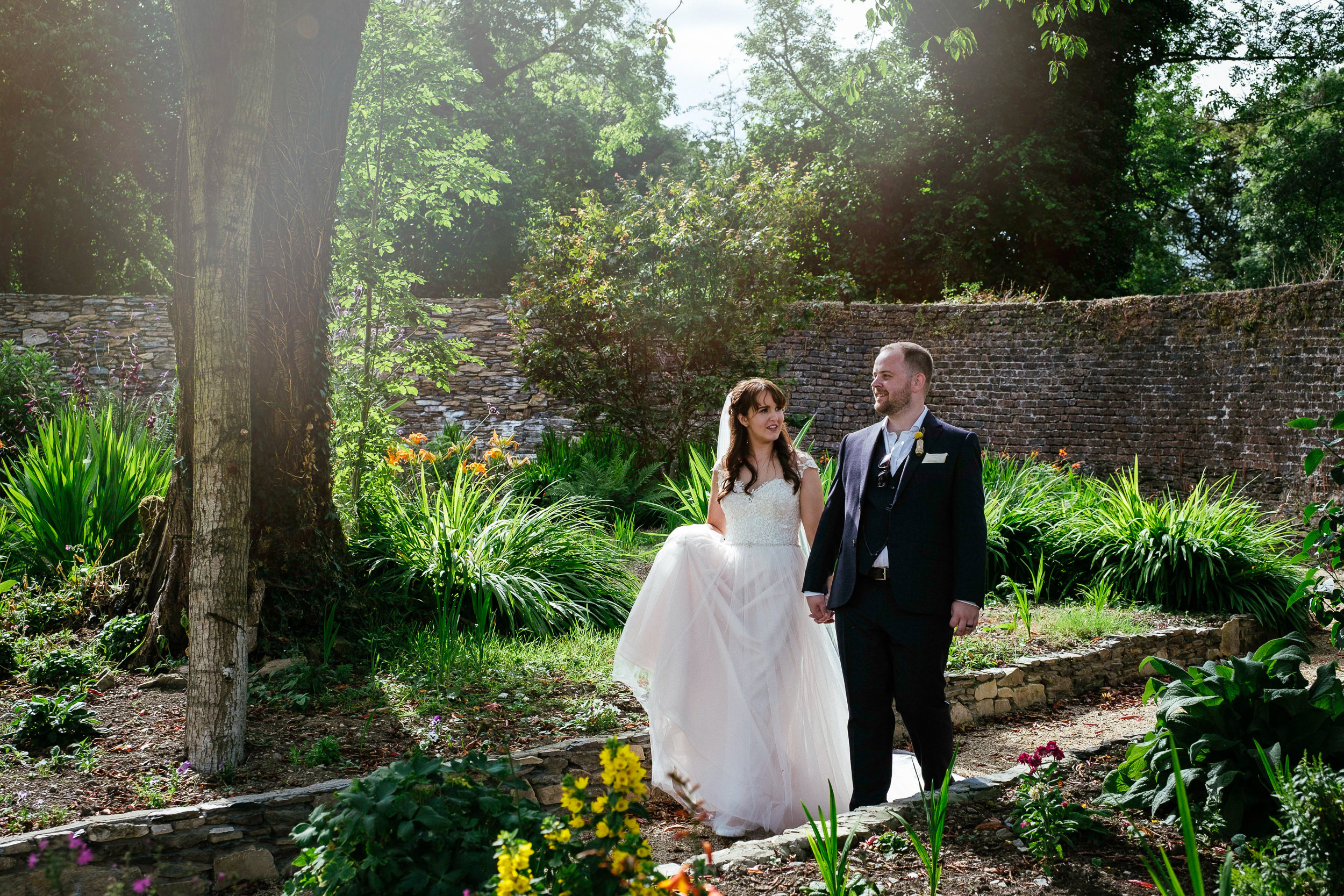 bride and groom walking in garden during their summer wedding at ballybeg house Co Wicklow