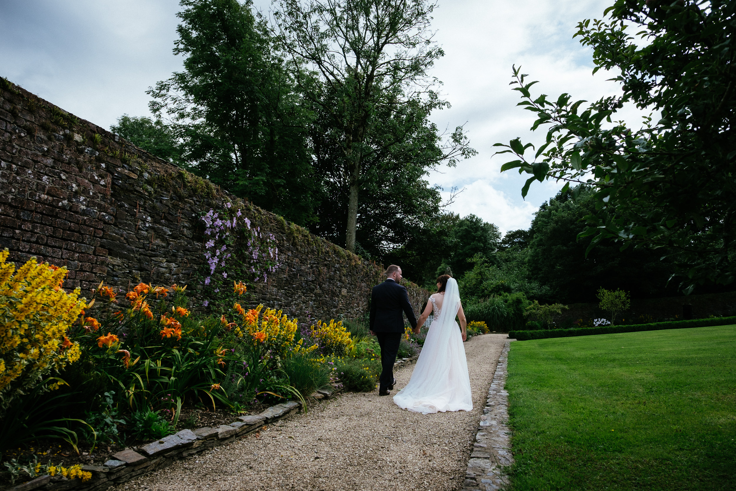 bride and groom walking away from camera in ballybeg house