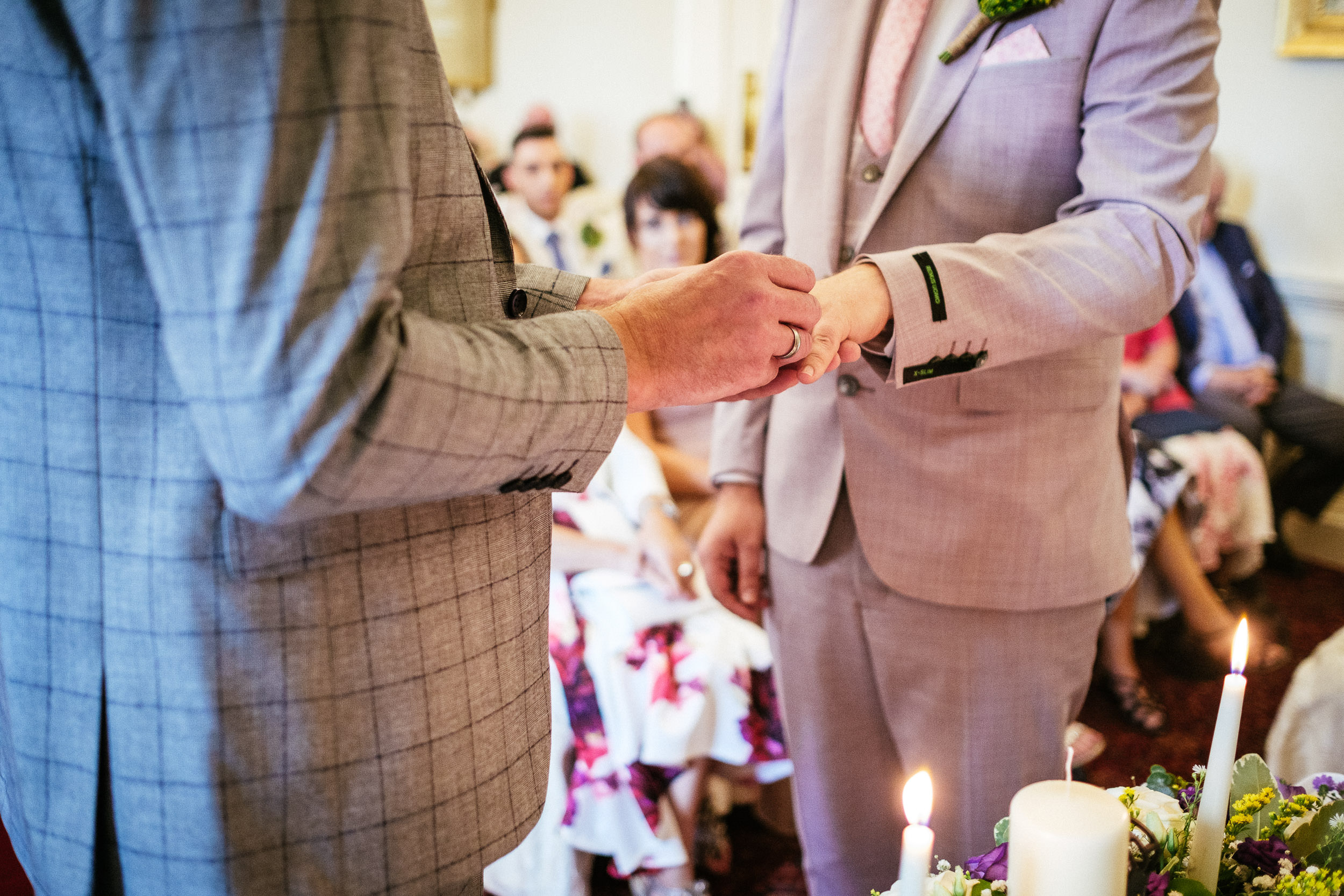 grooms exchanging wedding rings during their ceremony