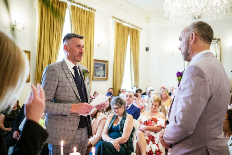 gay groom reading his vows