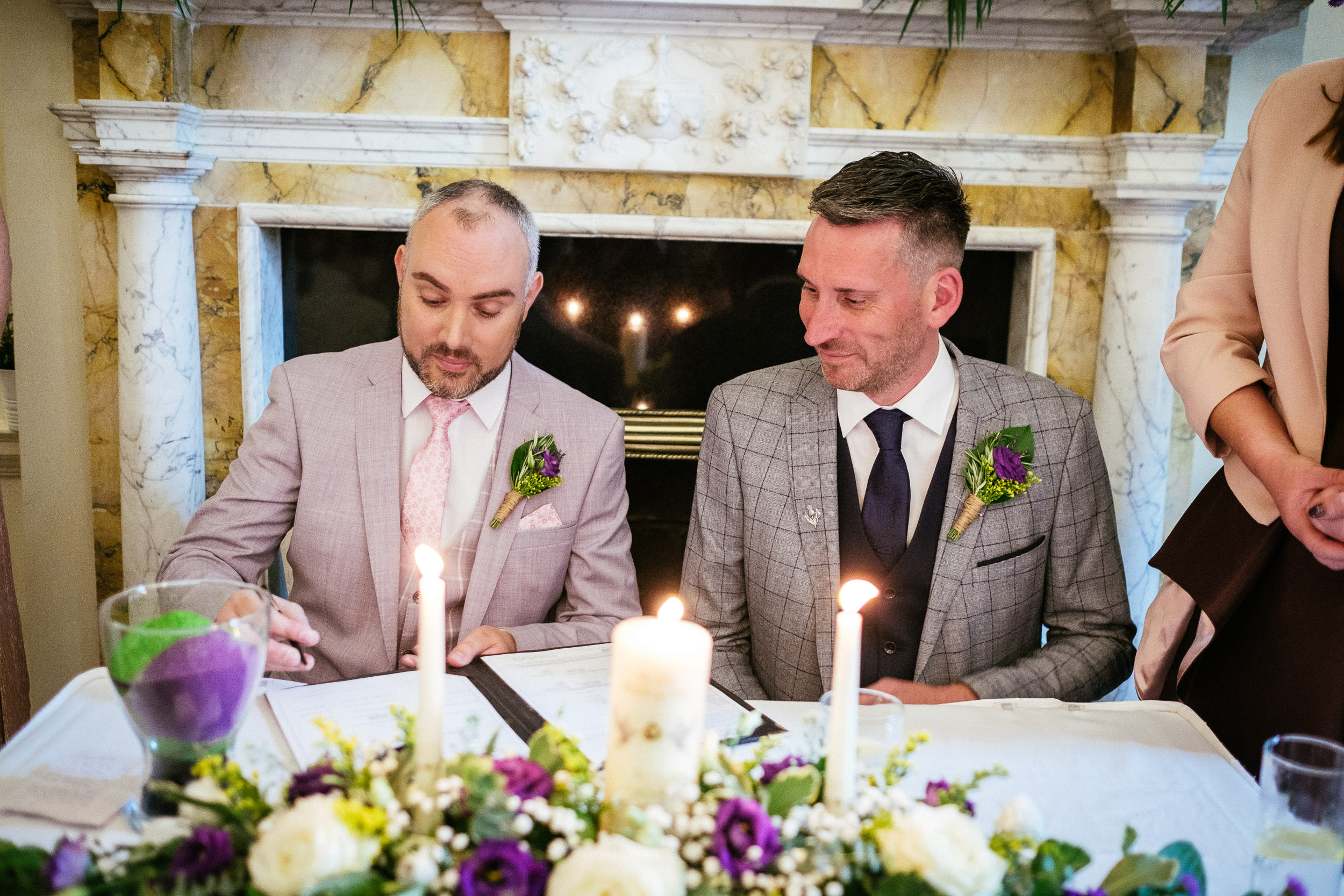 2 gay grooms signing their wedding register