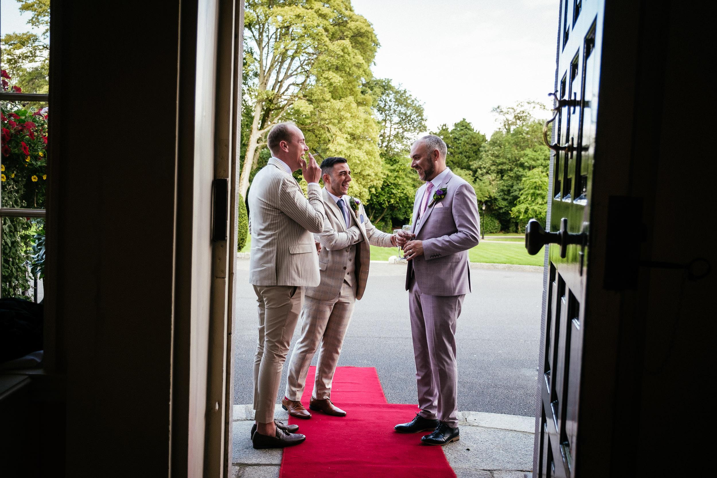 groom and groomsmen talking in doorway