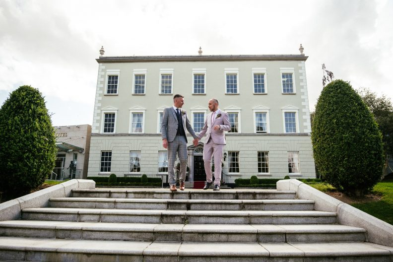 two gay grooms holding hands in front of dunboyne castle