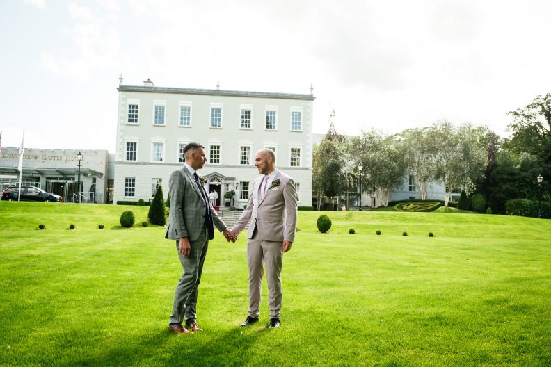 two gay grooms holding hands and chatting in front of dunboyne castle