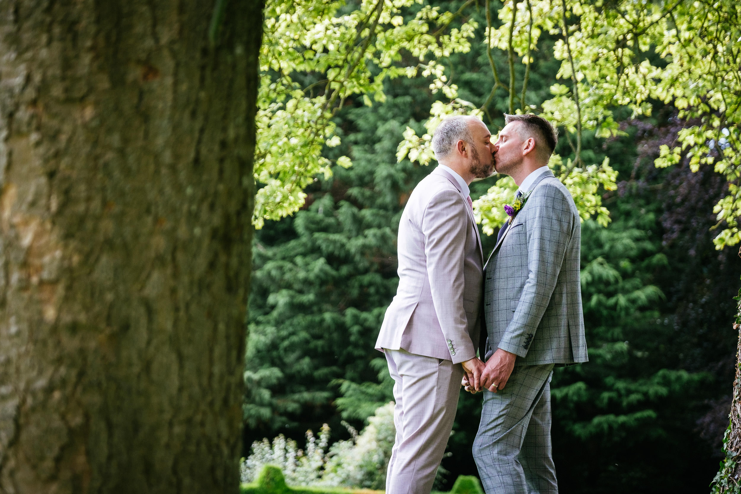 two gay grooms kissing under a tree in front of dunboyne castle