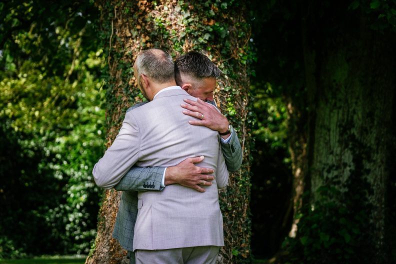 two gay grooms hugging ing under a tree in front of dunboyne castle