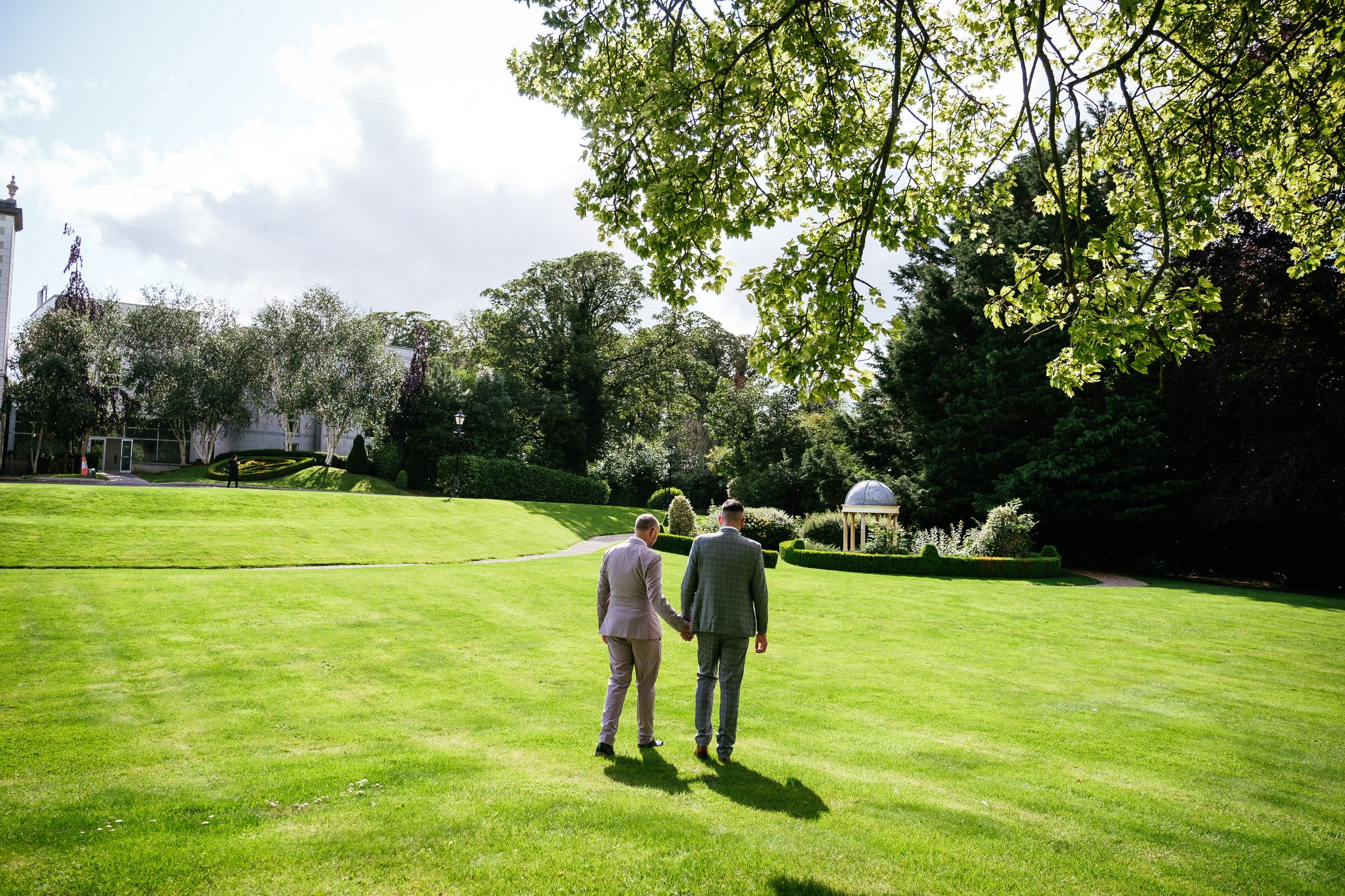 two gay grooms kissing in the gardens at dunboyne castle