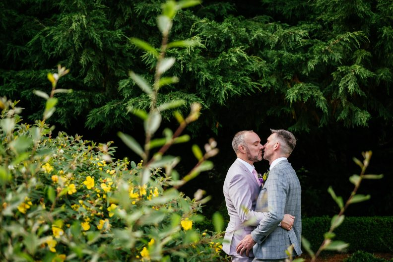 two gay grooms kissing by a tree
