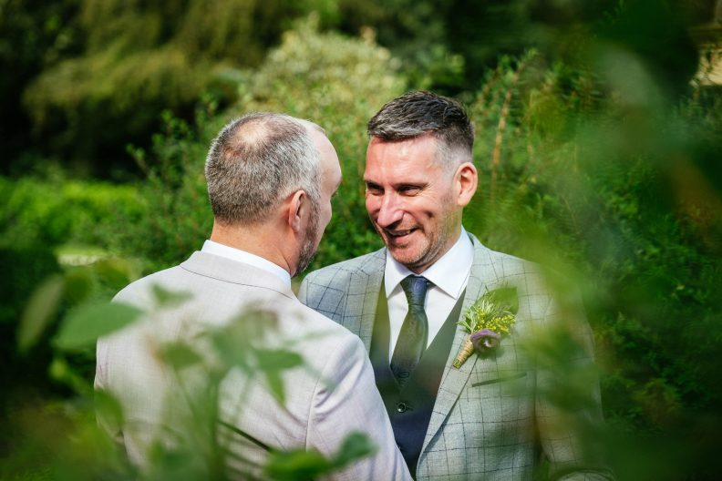 two gay grooms talking to each other