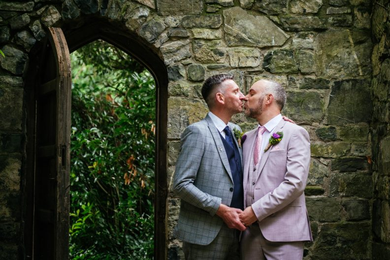 two gay grooms kissing by an archway at dunboyne castle