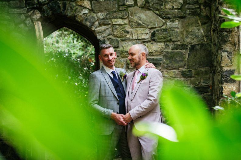two gay grooms kissing and laughing by an archway at dunboyne castle