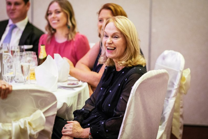 seated wedding guest laughing