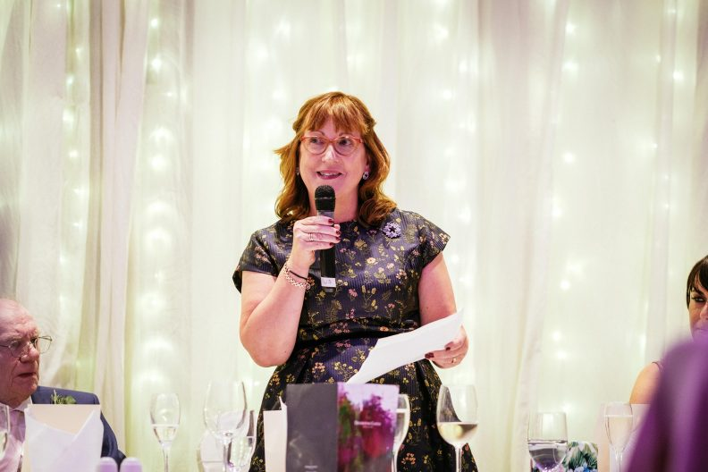 woman talking into a microphone during a wedding speech