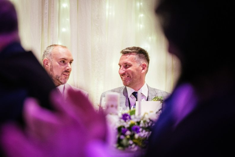 gay grooms laughing during a wedding speech