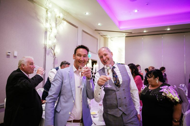 two wedding guests saying cheers