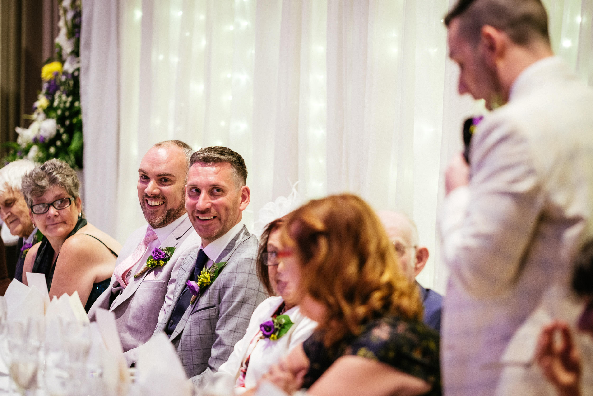 groom laughing at a wedding speech