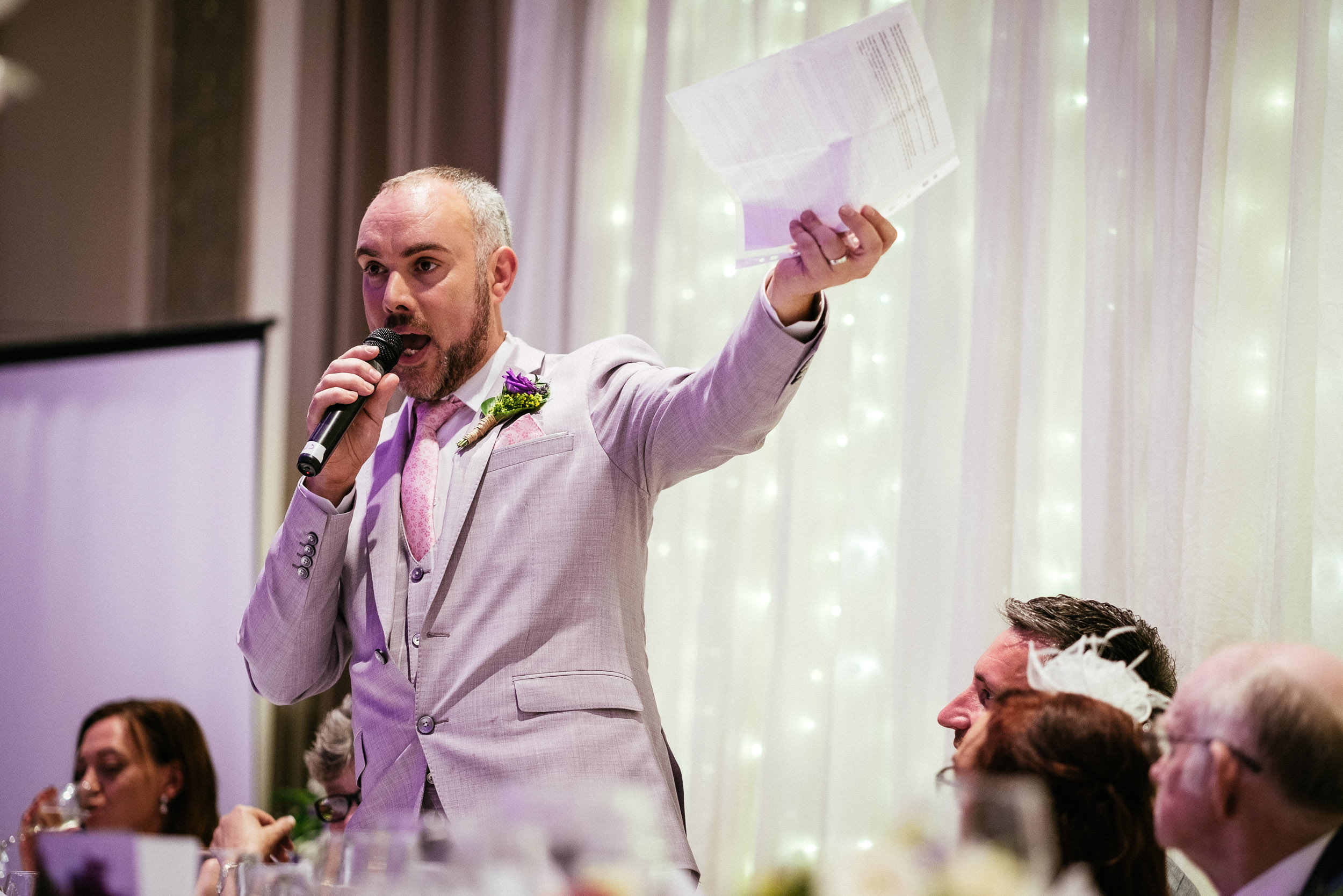 groom showing a piece of paper during his wedding speech